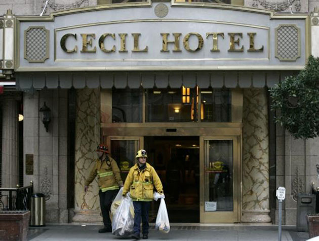 Firemen leaving the Cecil Hotel with white trashbags